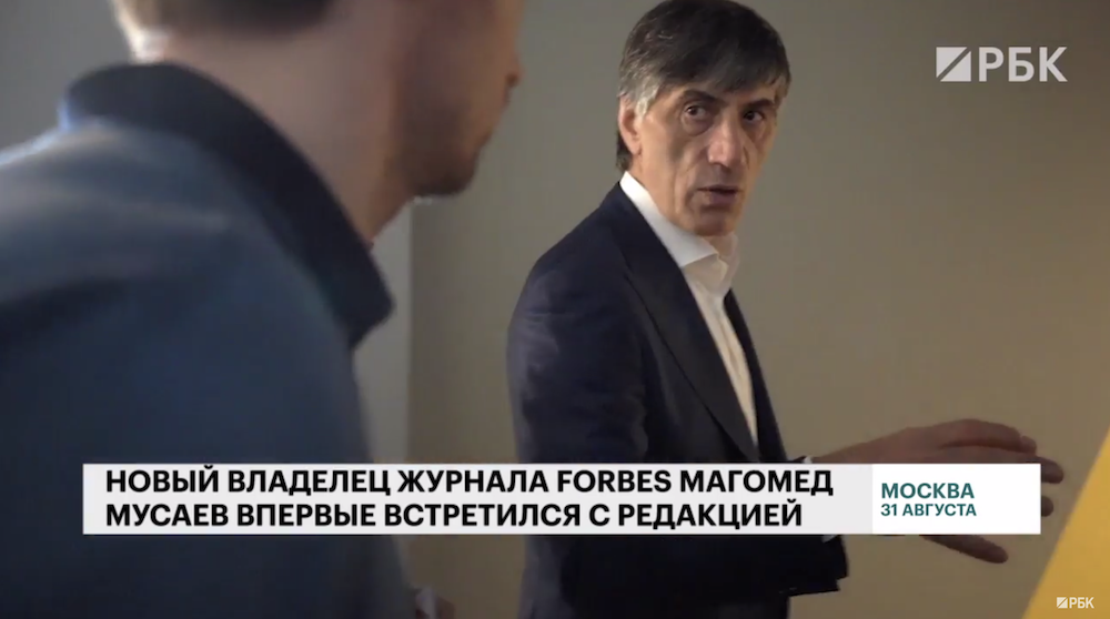 A screenshot from a Russian news report about Magomed Musaev's purchase of <em> Forbes Russia </em>