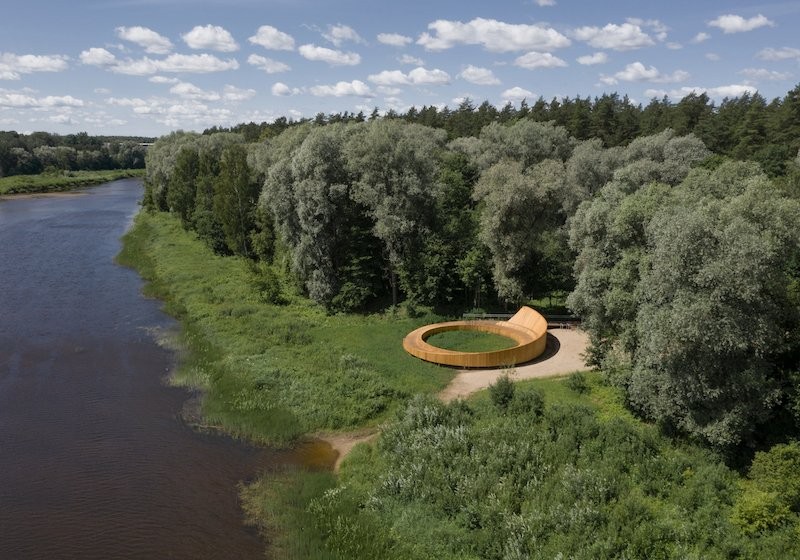 This curved wooden terrace carves an elegant path through Latvia's picturesque forest