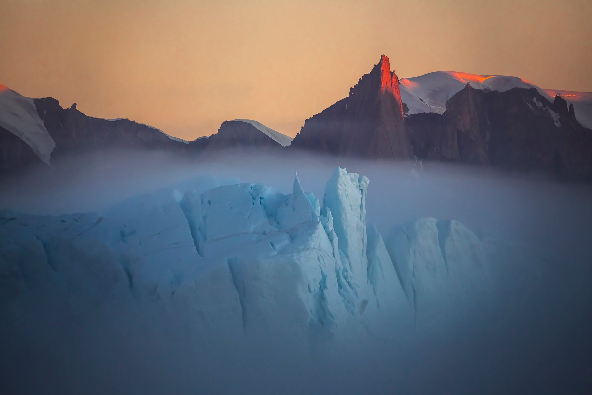 """""""Fog over the iceberg in Greenland. A very rare natural phenomenon. This is a huge iceberg that swam past the coast, shrouded in fog."""" Image: Vladimir Alekseev/www.tpoty.com"""