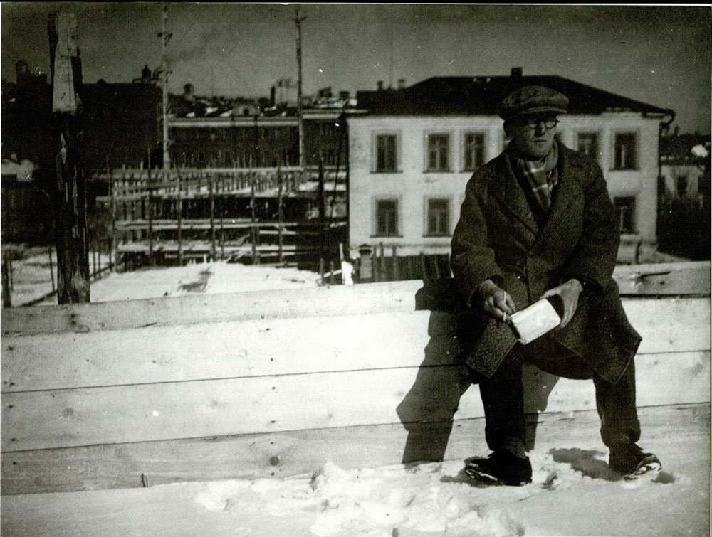 Le Corbusier sits in the snow in front of the Tsentrosoyuz building construction site in 1931