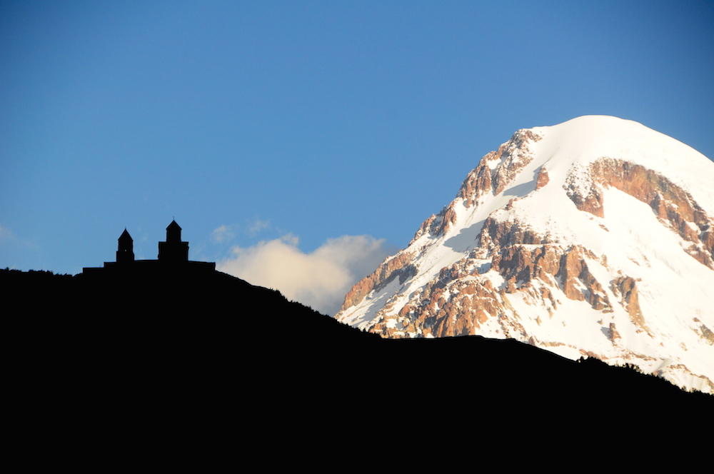 The Trinity Church above Stepantsminda, with Mount Kazbek in the background. Image: Panegyrics of Granovetter under a CC licence