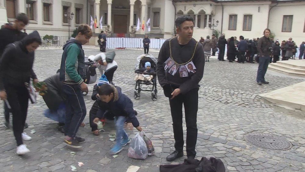 Alexandru Solomon throws money to the ground outside the Bucharest Orthodox Cathedral as part of his performance-protest