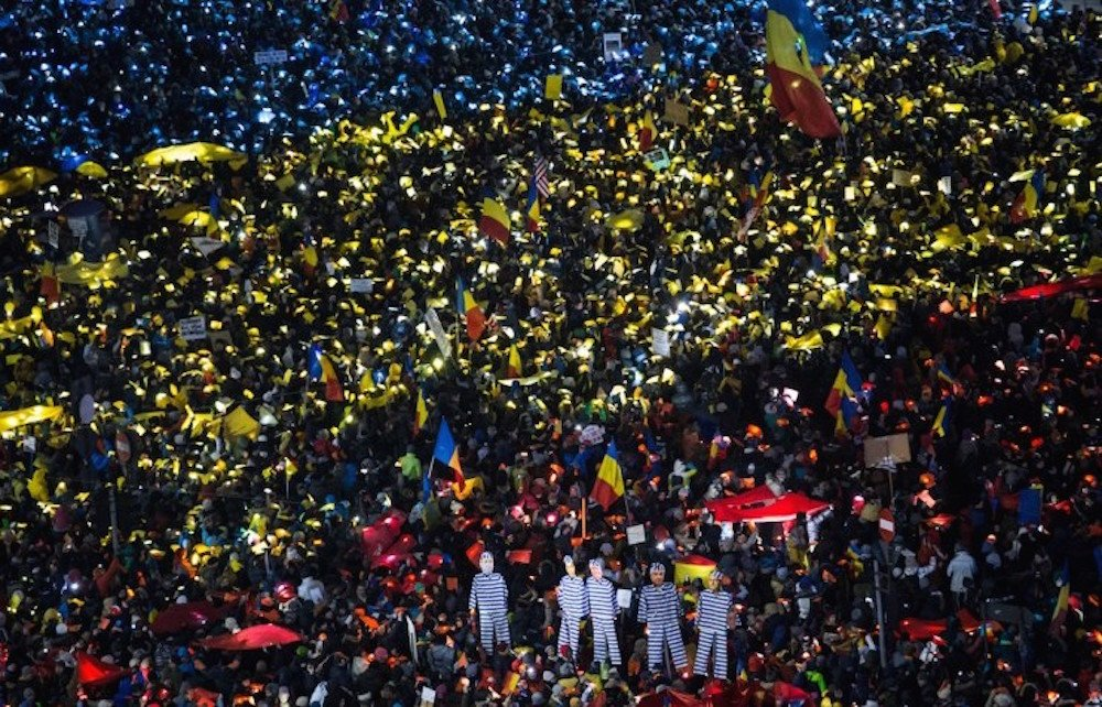 Protesters in Bucharest hold up coloured lights and objects to create the image of the Romanian flag during recent anti-corruption protests. Image: Ioana Moldovan