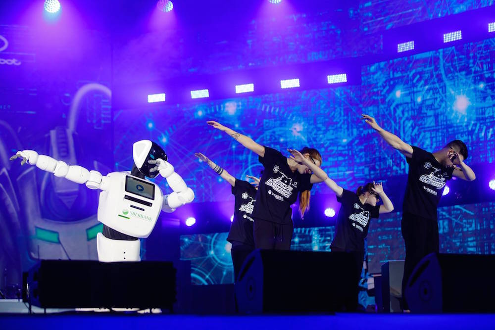 """Dancers """"dab"""" with a robot branded with the Sberbank logo — a far cry from the Festival's communist origins. Image: World Festival of Youth and Students 2017/Facebook"""
