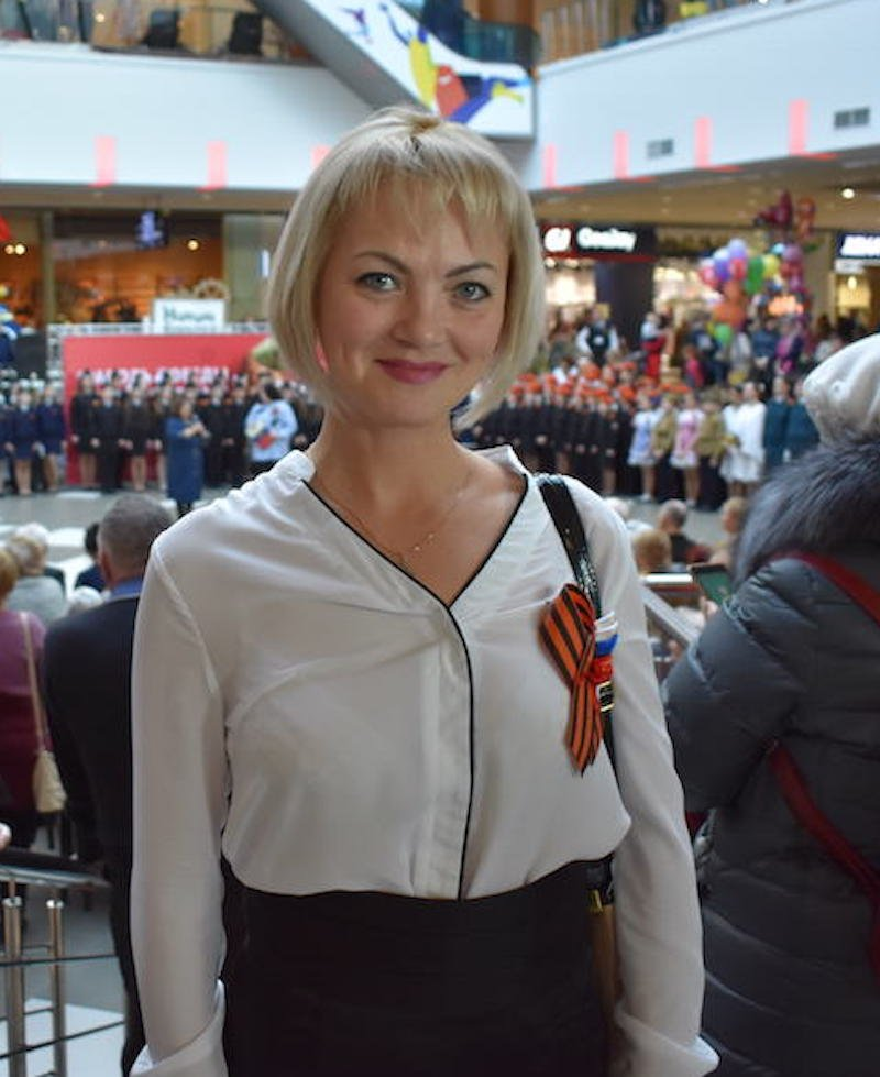 Teacher Irina Kirpikova watches as her pupils perform war-themed songs and dances in a shopping mall