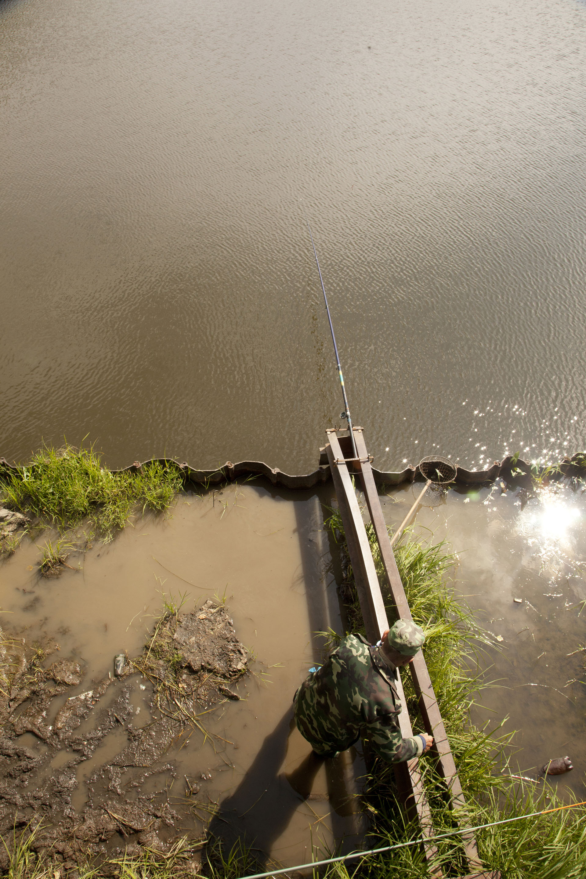 A man sets up his fishing pole under a bridge in town