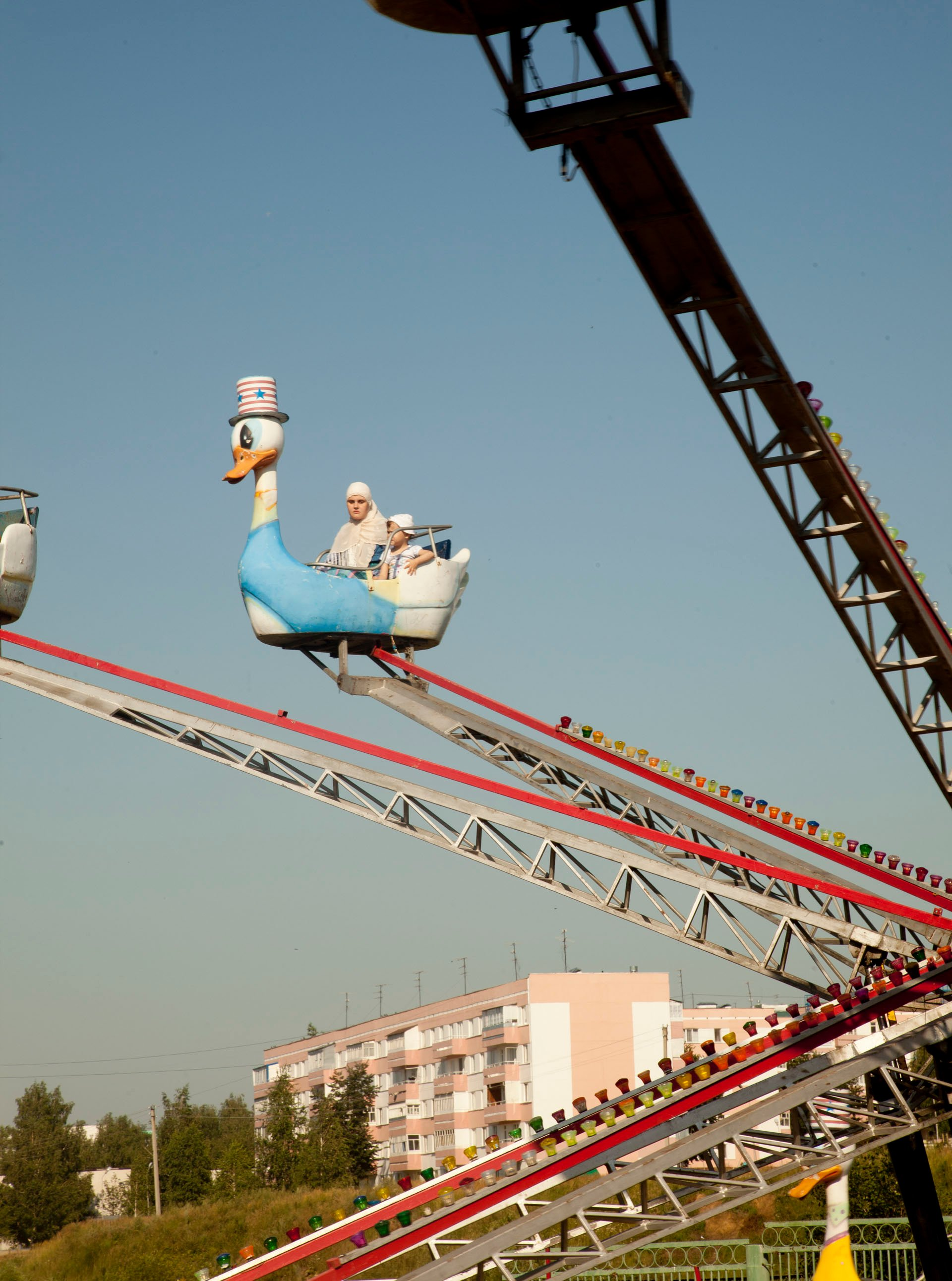 A woman and child are the only two on a carnival ride in Kamskie-Polyani