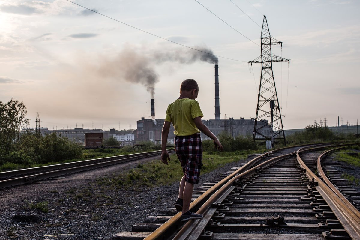 A boy walks on a railway track. Since the mid-2000s, many of Vorkuta's schools and kindergartens have been abandoned and closed