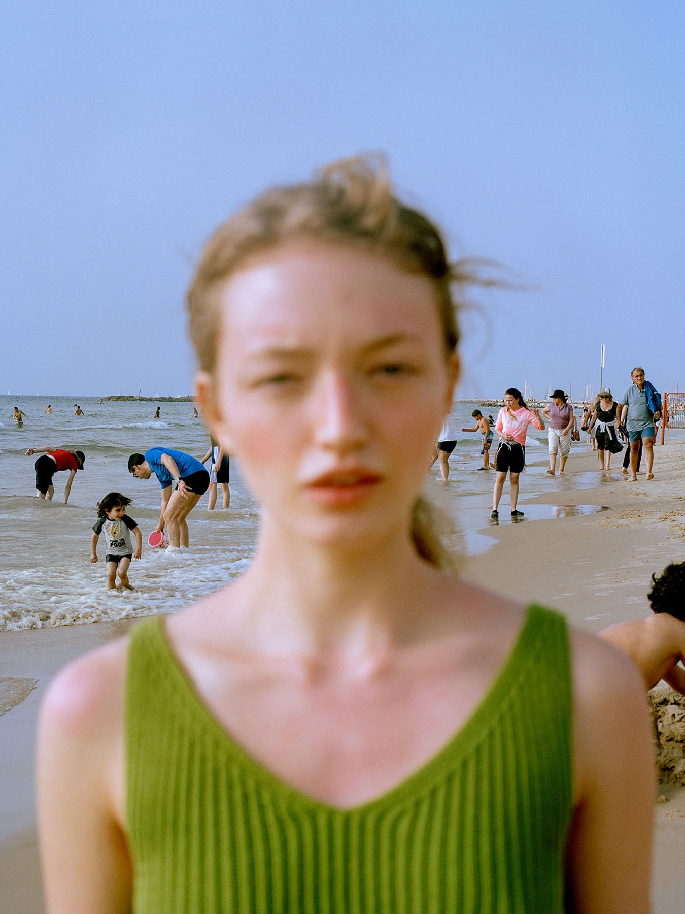 <p>Emmie America often works with fashion photography, but portraiture, movement and capturing each person's character is central to her practice. This photo was taken on a beach in Tel Aviv, reflecting its hectic surroundings in the blazing sun. </p>