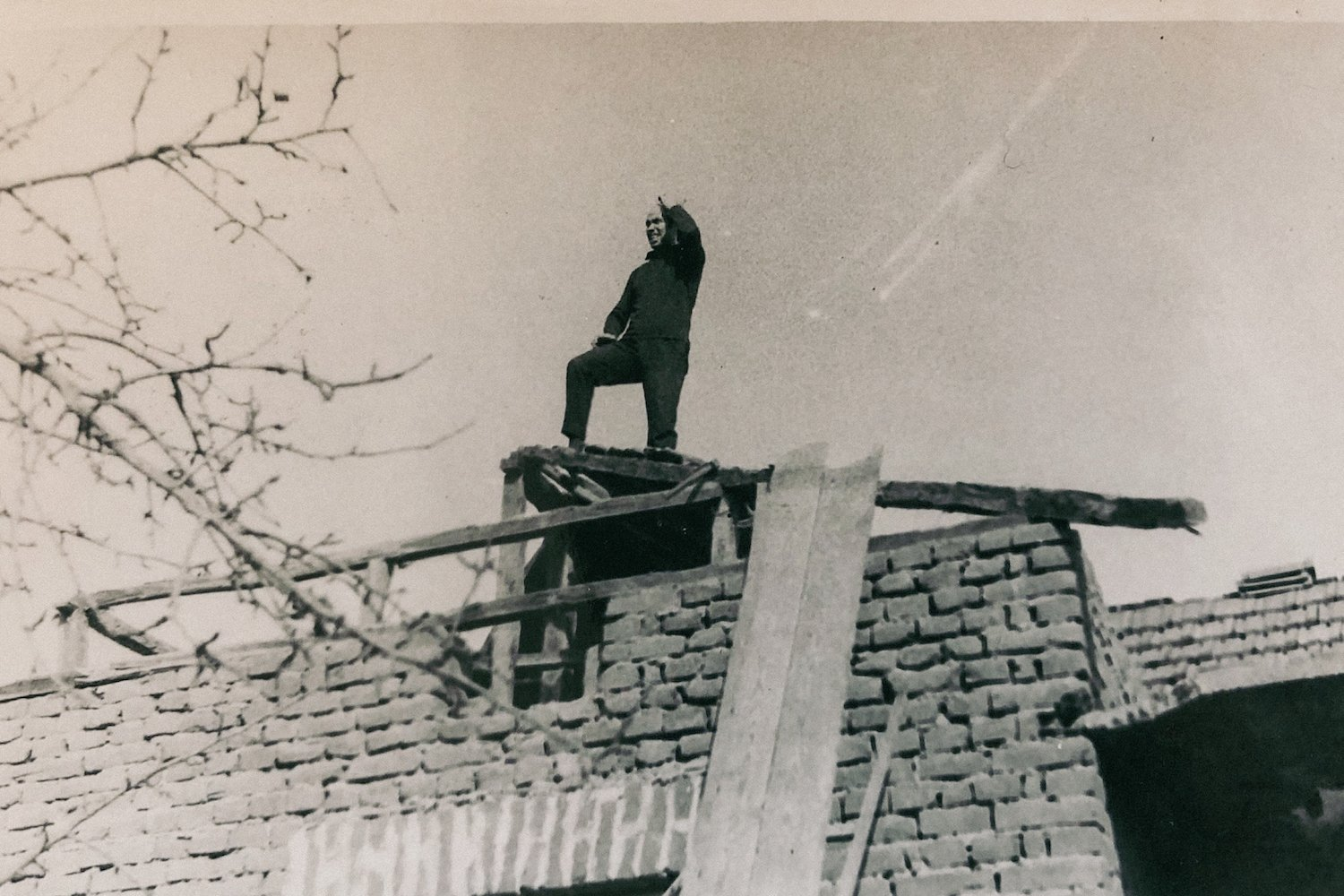 A man stands atop the ruins of his house in Zhivovtsi.